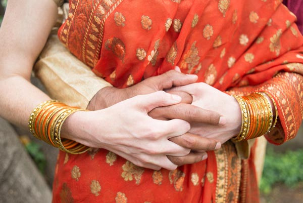 Hands of bride and groom interlaced after wedding; bride wearing red sari.