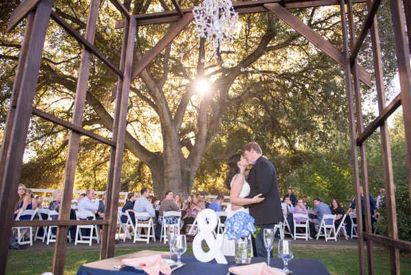 Bride and groom kissing with guests and setting sun in background during outdoor Napa wedding reception ,
