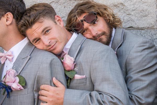 Funny groomsmen cuddling on each other's shoulders in front of stone wall at downtown San Francisco wedding.