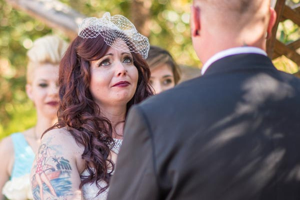 Bride fighting back tears during wedding ceremony at Monterey Whaling Station Adobe.