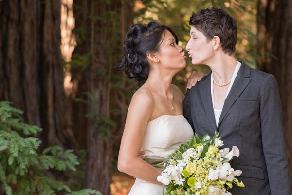 Funny photo of brides kissing with redwoods in background at The Pavilion at Redwood Estates.