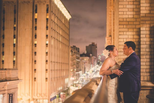 Bride and groom facing one another on balcony over downtown San Francisco street lights at Elks Lodge.