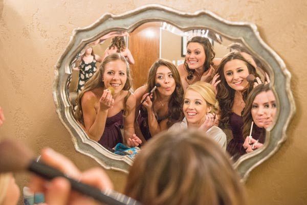 Smiling bride getting ready in mirror with bridesmaids before wedding at Casa Real Ruby Hill Winery.