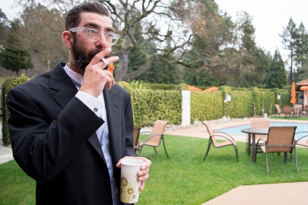 Groomsman waiting outside with cigarette and coffee before wedding ceremony at Sequoyah Country Club.