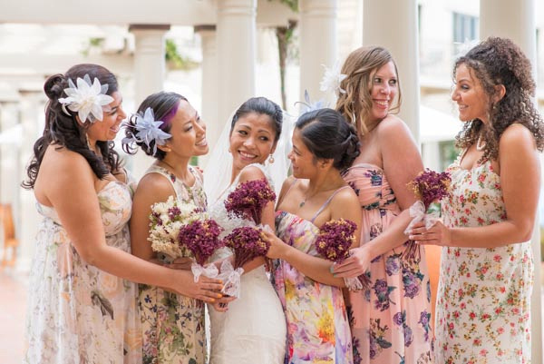 Bridesmaids wearing floral dresses with bride before outdoor wedding ceremony at Monterey Plaza Hotel & Spa.