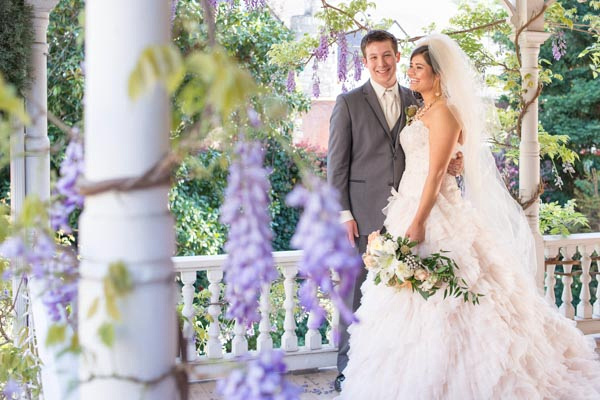 Young bride and groom pose on white Victorian balcony surrounded by vines with purple blossoms at The Seasons Bed & Breakfast in Placerville.