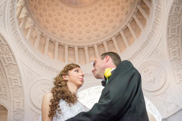 Bride and groom looking into each other's eyes after wedding elopement ceremony with dome ceiling in background at San Francisco City Hall.