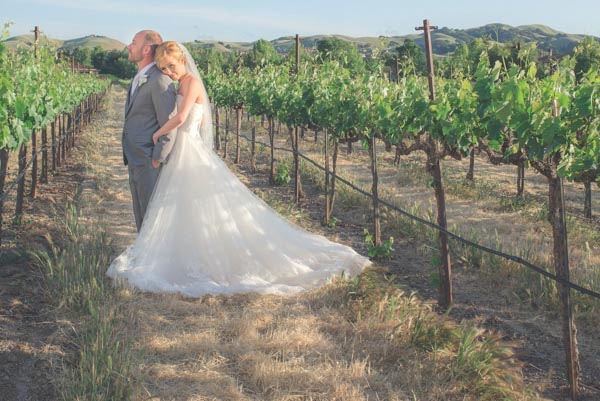 Bride in vineyard resting head on groom's shoulder from behind at Casa Real Ruby Hill Winery.