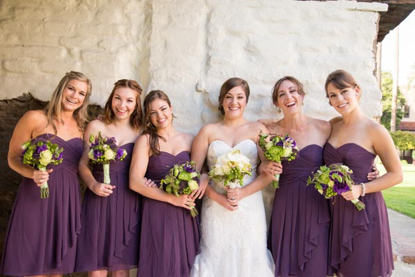 Bride and her bridesmaids posing in front of old white brick wall at Santa Clara Mission Church.
