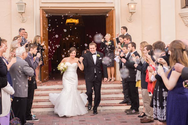 Bride and groom exiting ceremony while guests blow bubbles at Santa Clara Mission Church