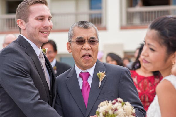Smiling father giving away bride at outdoor wedding ceremony at Monterey Plaza Hotel & Spa.