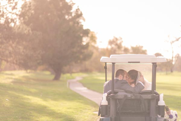 Bride and groom kissing in golf cart after wedding ceremony at Rancho Canada Golf Club in Carmel.