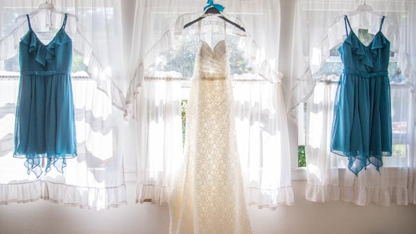 Elegant wedding dress and blue bridesmaid dresses hanging in front of sunlit window.