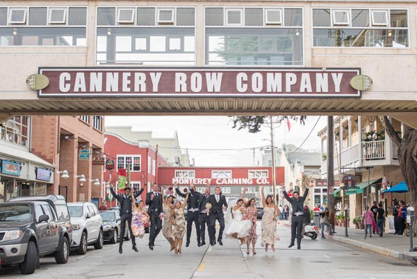 Bridal part jumping in middle of street at cannery row after wedding ceremony in Monterey.