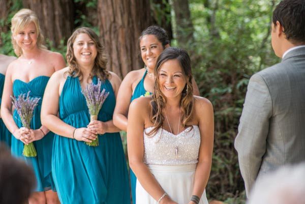 Beautiful laughing bride during ceremony with redwoods and bridesmaids in background at Hazlwood in Lost Gatos.