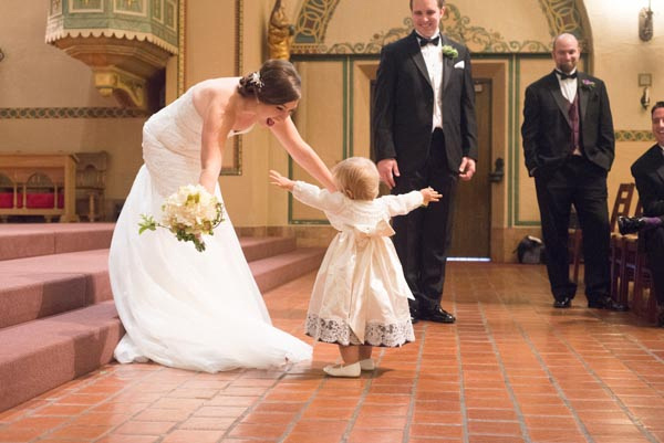 Toddler walks to bride to give hug after wedding ceremony at Santa Clara Mission Church.