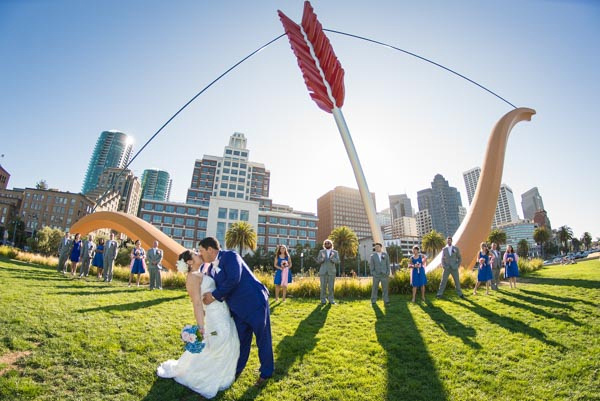 Groom dipping bride and kissing her with bridal party and cupid's span in background in San Francisco.
