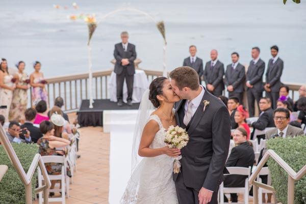 Bride and groom kissing after outdoor wedding ceremony with guests and ocean in background at Monterey Plaza Hotel & Spa.