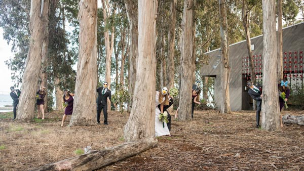 Funny bridal party hiding behind eucalyptus trees wearing animal masks before wedding at Curiodyssey,