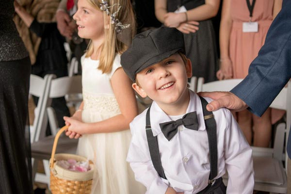 Cute ring bearer smiling at camera during wedding ceremony at Sequoyah Country Club.