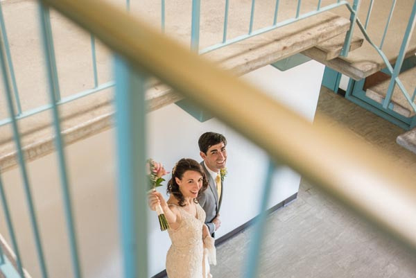 Bride and groom looking up from below stairway after wedding ceremony.