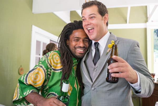 Smiling groom holding beer and hugging guest during wedding reception at Hazlwood.