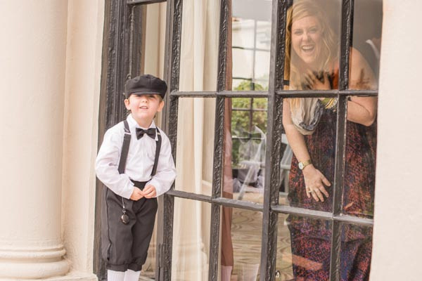 Cute ring bearer outside of window while woman smiling from inside at Sequoyah Country Club.