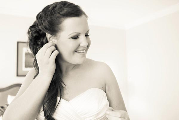 Beautiful bride putting on earrings before wedding ceremony at St. Claire Hotel in San Jose.