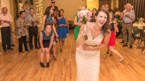 Bride laughing on dance floor before bouquet toss with guests in background during wedding reception.
