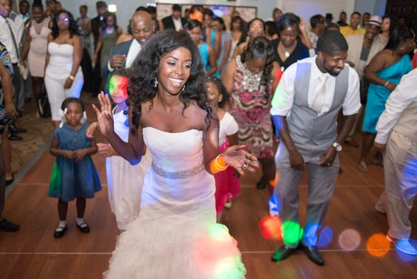Bride dancing with groom and guests in background, colorful dj lights flashing during reception at Sequoyah Country Club.