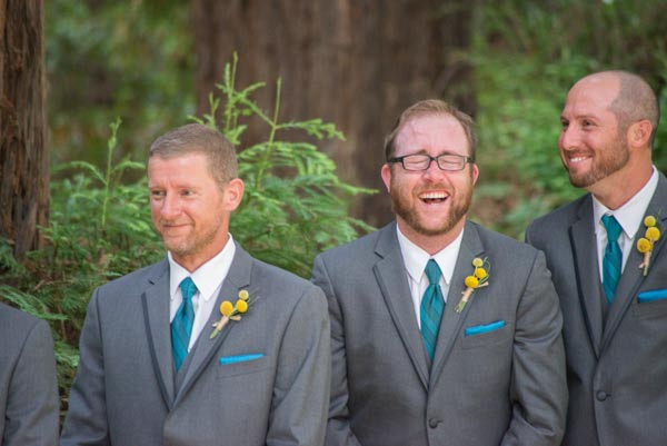 Groomsmen laughing during outdoor wedding ceremony amidst redwood trees at Hazlwood in Los Gatos.