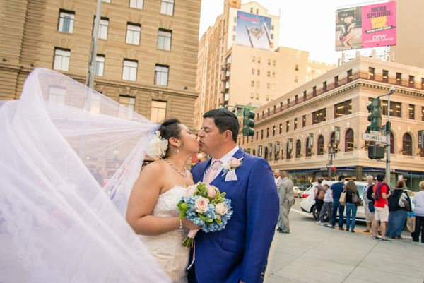 Bride and groom kissing on sidewalk, her flowing veil blowing in the breeze in downtown San Francisco.